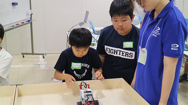 EV3でプログラムを実行する小学生