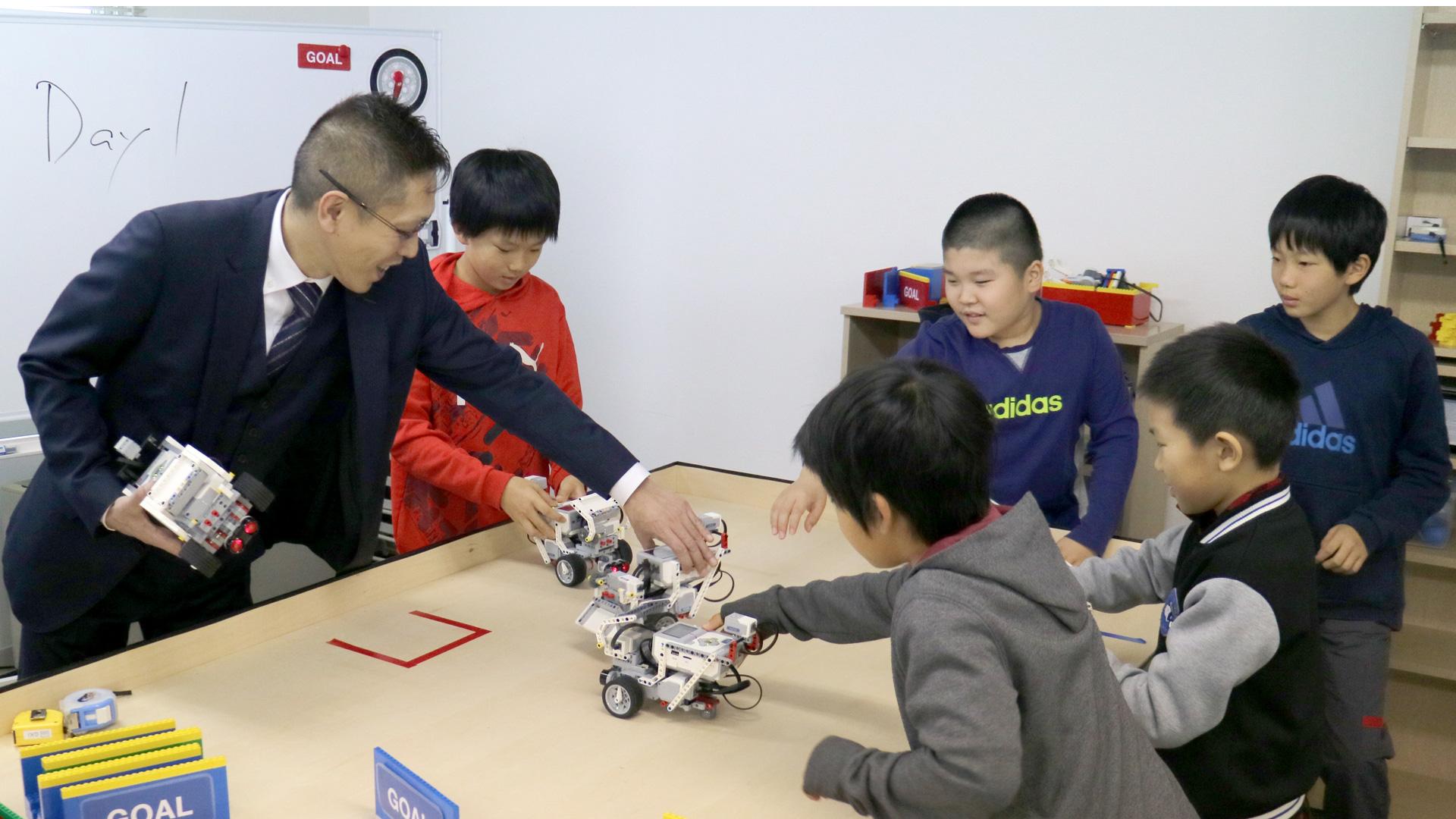 EV3でプログラムを実行する子どもたち